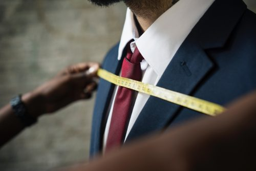 オーダースーツの採寸をされる男性