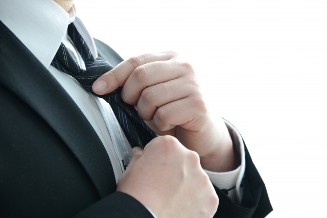 ネクタイを締めようとする男性