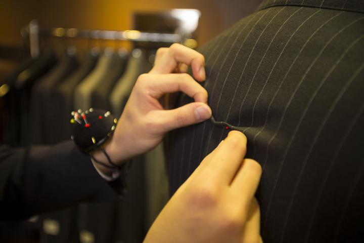 スーツの補正をするスタッフ