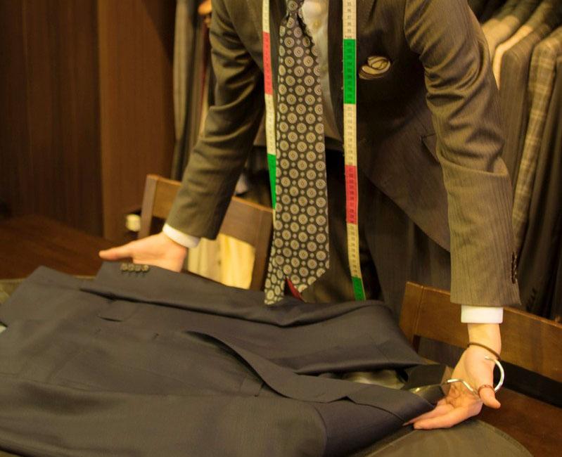 スーツを見せるスタッフ