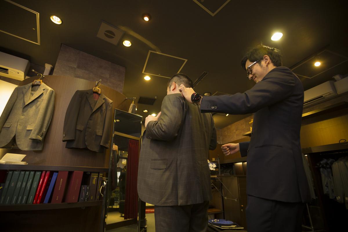 スーツを試着するお客様とスタッフ