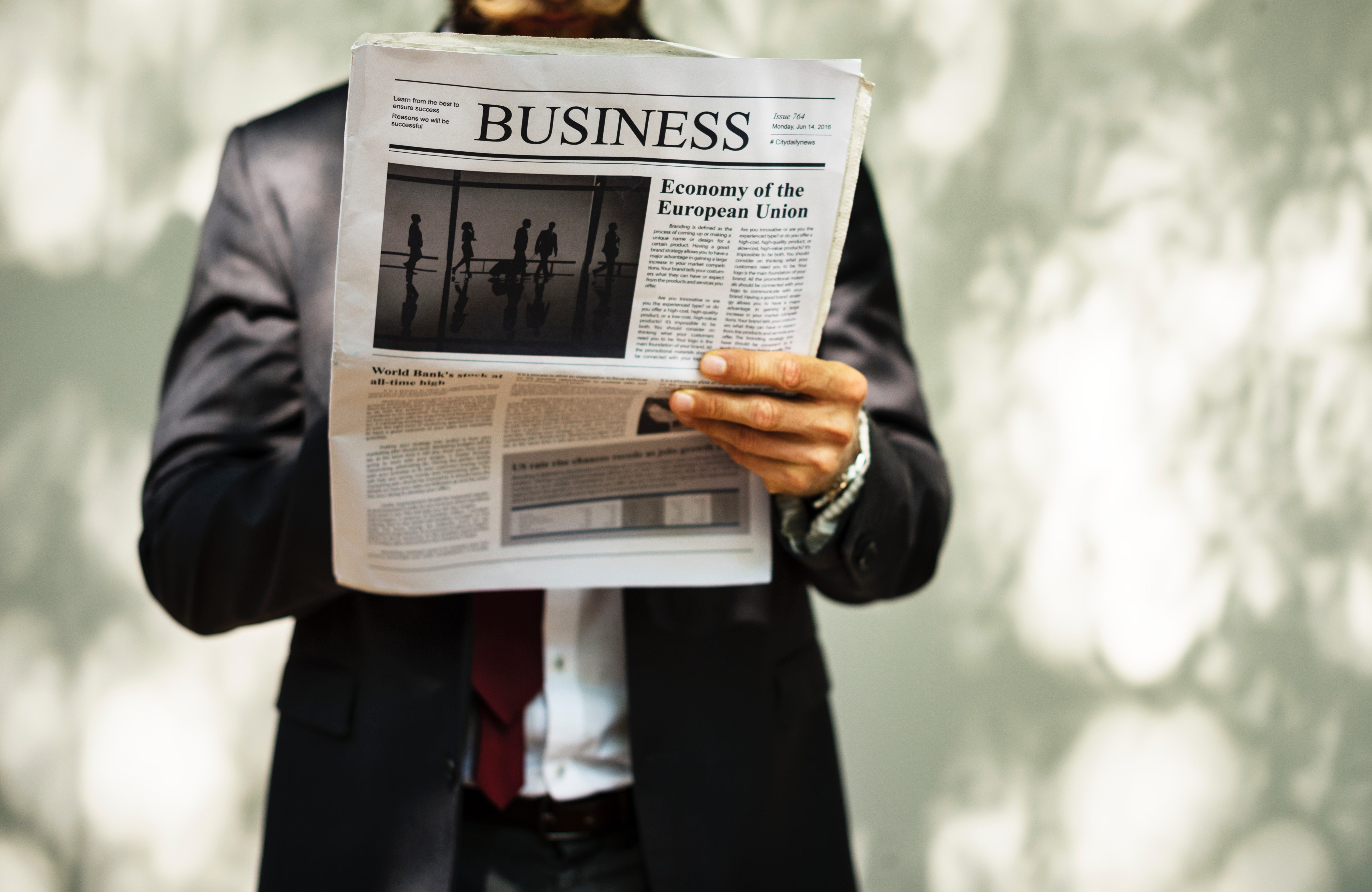 新聞を手に持ったビジネスマン